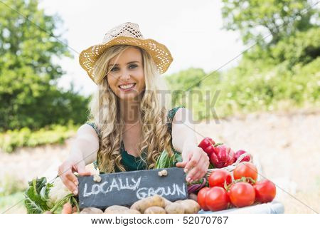 Happy young female farmer standing at her stall at the farmers market smiling at the camera