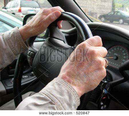 Elderly Hands At Steering Wheel