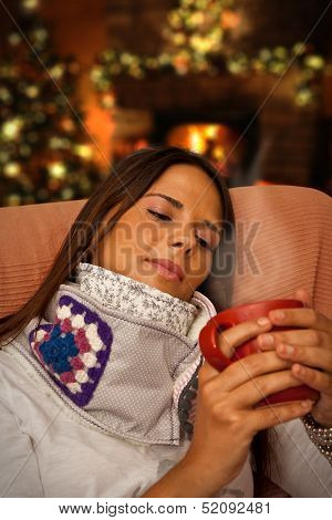 Woman Having Hot Drink Seating Near Christmas Tree And Fireplace