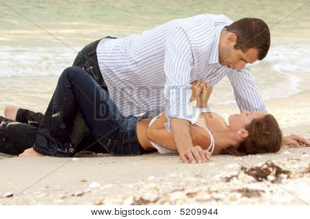 Woman Is Unbuttoning Shirt On Man As They Lay On The Beach