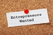 The phrase Entrepreneurs Wanted typed onto a scrap of lined paper and pinned to a cork notice board poster