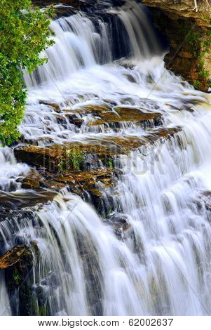 Beautiful cascading waterfall flowring over natural rock formation poster