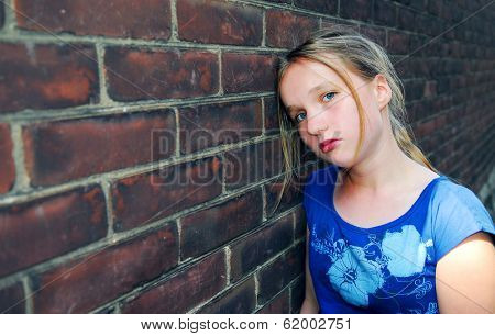 Young girl near brick wall looking upset