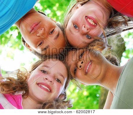 Faces of four happy young girls shot from below