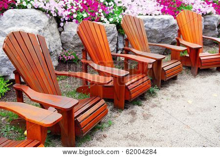 Row of solid wood patio chairs and natural stone landscaping