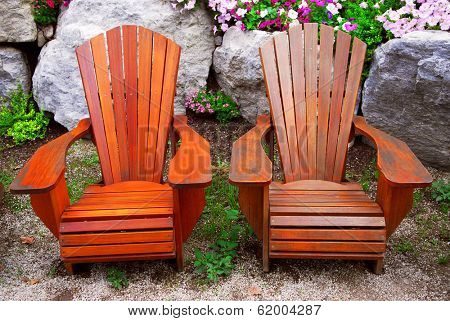Two solid wood patio chairs and natural stone landscaping
