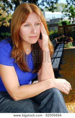 Mature woman looking sad and stressed sitting on a park bench