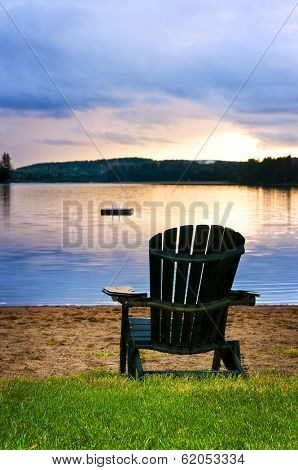 Wooden chair on beach of lake at sunset
