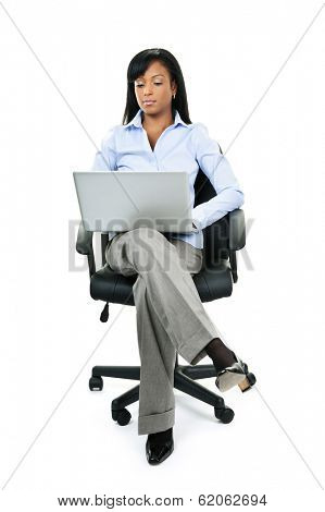 Young serious black woman sitting in leather office chair with laptop computer