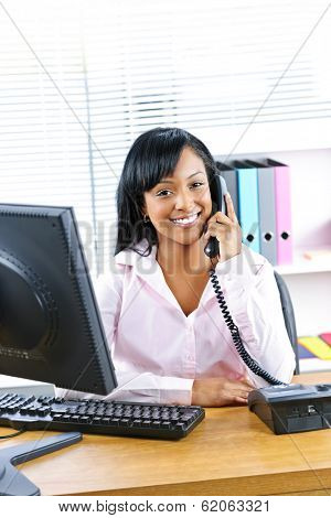 Smiling young black business woman on phone at desk in office