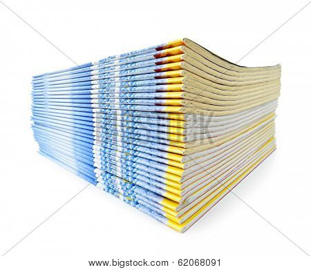 Many magazines stacked in a pile isolated on white