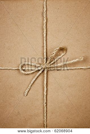 Gift package wrapped in brown paper tied with twine closeup