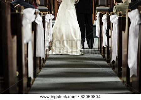 Bride and groom getting married in church view from aisle