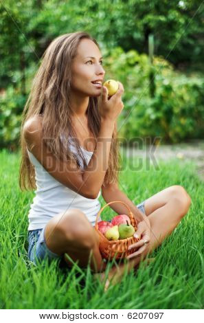 Beautiful Womenl Eating Pear On The Green Grass