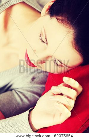 Closeup portrait of a young beautiful woman hugging to a red pillow, holding her hend next to the face.