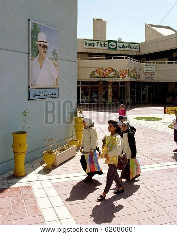 BAGHDAD, IRAQ - MARCH 11: Under the watchful eye of Iraqi president Saddam Hussein,  women search for bargains at the Iraqi Club mall in central Baghdad on March 11, 1999 in Baghdad, Iraq.