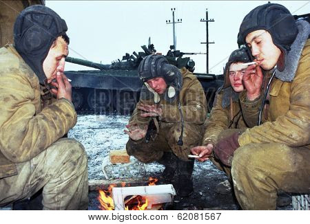 GUDERMES, CHECHNYA - JAN 16: Russian army armor troops try to keep warm, and catch a few minutes rest between fighting Chechen rebels in Gudermes, Chechnya, on Sunday, January 16, 2000.
