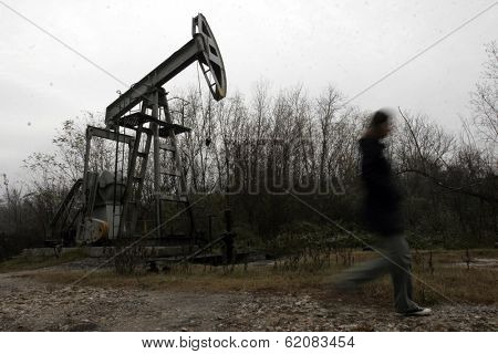 PLOIESTI , ROMANIA - NOV 8: A woman walks past a  pump jack owned and operated by Romanian oil and gas company S.C. Petrom S.A. near Ploiesti, Romania, on Thursday, November 8, 2007.