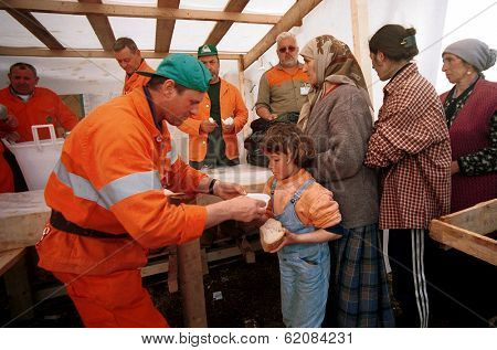 KUKES, ALBANIA,  18 APRIL 1999 --- Italian aid workers feed thousands of Kosovar Albanian refugees at a camp in northern Albania.  Tens of thousands of ethnic Albanians have fled Kosovo.