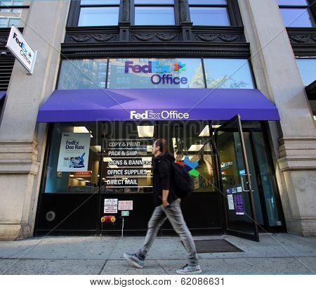 NEW YORK CITY - OCT 20 2013: Pedestrians walk past a FedEx Store retail shop in Manhattan on Sunday, October 20, 2013.