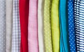 Many different fabrics linen napkins of different colors a stack of kitchen towels closeup poster