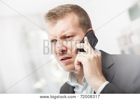 Anxious Businessman Taking A Mobile Call