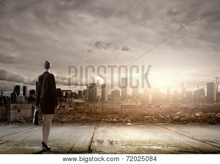 Rear view of businesswoman looking at ruins of city