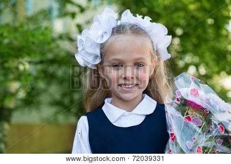 First grader girl with flowers in their first day of school. Russia.