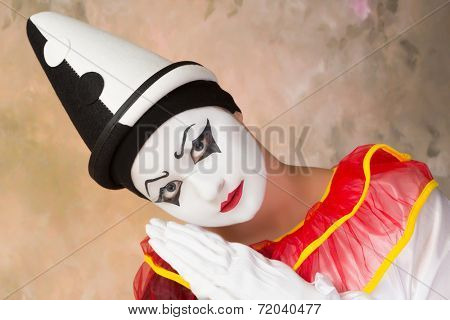 Female clown in pierrot disguise and real painted face