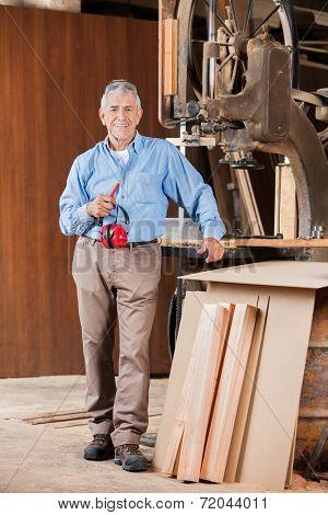 Full length portrait of senior male carpenter holding ear protectors by bandsaw in workshop