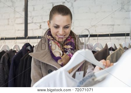 Smiling young woman choosing sweater in store