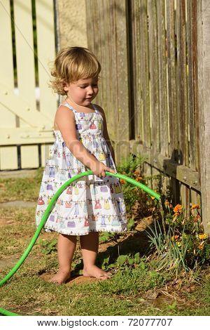Little gardener: Cute girl watering flowers in the garden
