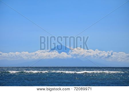 Far Away Silhouette Of A Volcano Under Sea Waters And Stripe Of Clouds