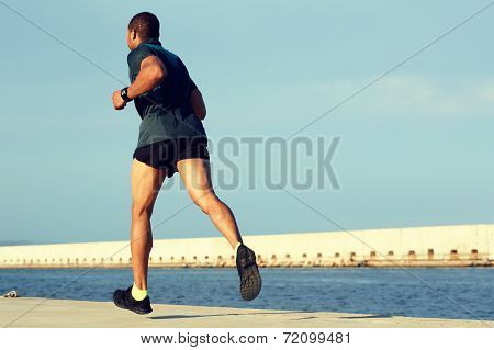 Dark skinner male runner jogging with high speed at sunny evening outdoors