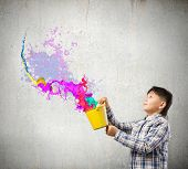 Young boy splashing colorful paint from bucket poster