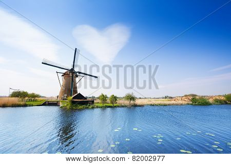 Water pumping mill and the canal with cloud in shape of heart in Kinderdijk, Netherlands, Europe poster