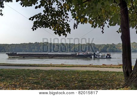 Tugboat with ship pass along the riverside park in Ruse town, Bulgaria poster
