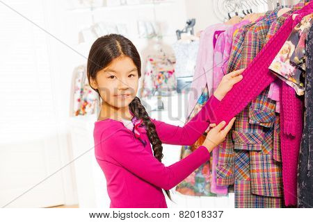 Asian girl with braid stands near clothes on the hangers in the shop and holding the chosen sweater's arm poster