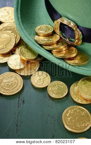 Happy St Patricks Day Leprechaun Hat With Gold Chocolate Coins On Vintage Style Green Wood Backgroun