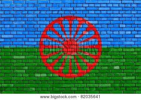 flag of Romani people painted on brick wall