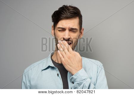 Young casual man yawning
