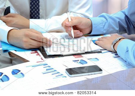 Business Colleagues Working Together And Analyzing Financial Figures On A Graphs