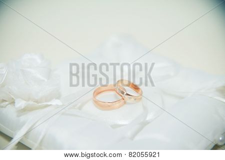 Two Gold Wedding Rings Lying On The White Pillow
