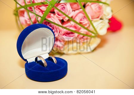 Wedding Rings In The Blue Box On The Background Of The Bride's Bouquet