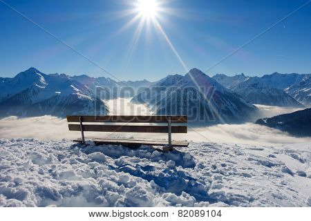 Bench with view over the winter Alps