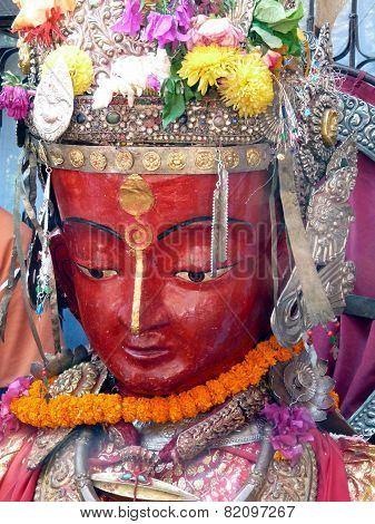 Red-faced Dipankar effigy adorned with jewels and floral offerings from Bhaktapur, Nepal poster