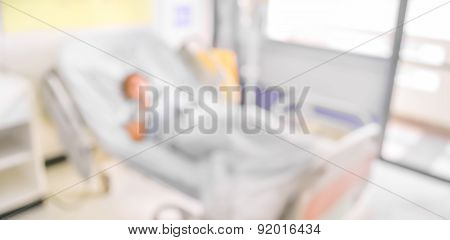 Blurred Image Of Patient With Drip In Hospital For Background Usage .