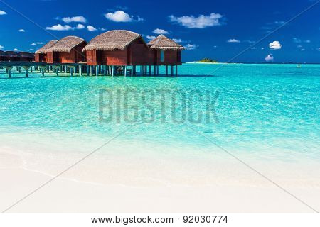 Overwater bungalow and white beach in blue lagoon of tropical Maldives