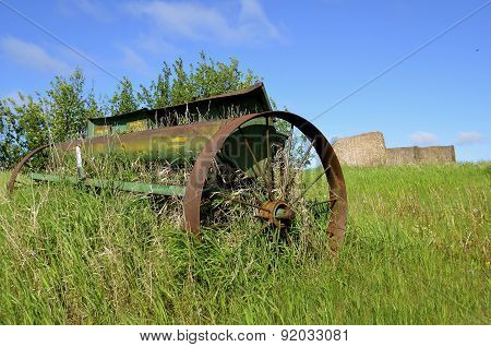 Old rusty grain seeder in a field