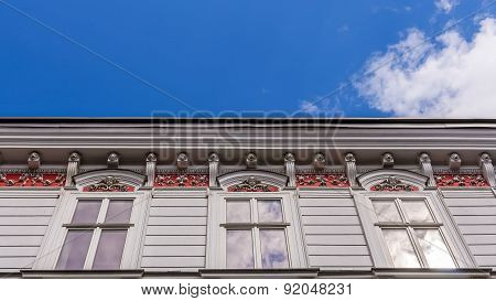 Facade of an ancient tenement with sunbeams reflecting in a window pane in Bielsko-Biala, Silesian Voivodship, Poland. poster